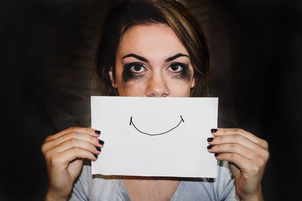 Sad woman with smudged mascara holding a smiley face over her mouth | Female Domestic Violence Attorneys for Women in California | Her Lawyer | Los Angeles