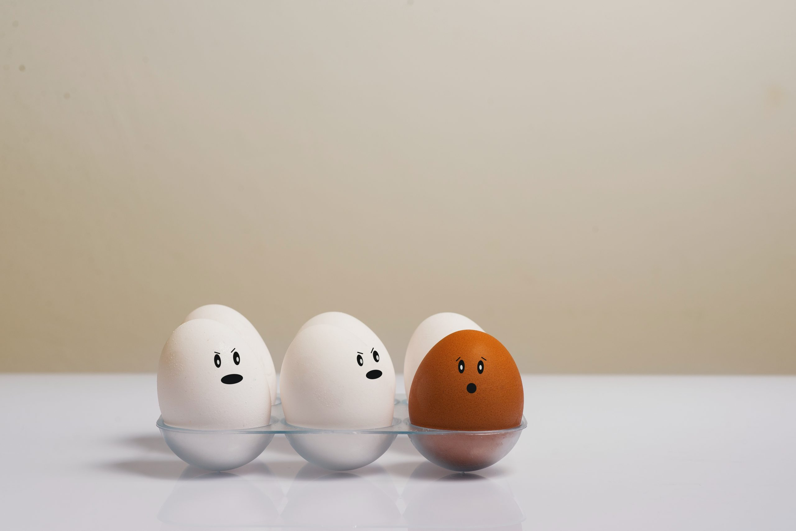 5 white eggs stare at a brown egg discriminatorily | Female Employment Discrimination Attorneys for Women in California | Her Lawyer