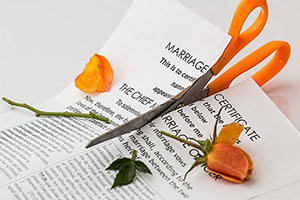 Scissors cut through a marriage c ertificate | Divorce Law | Her Lawyer